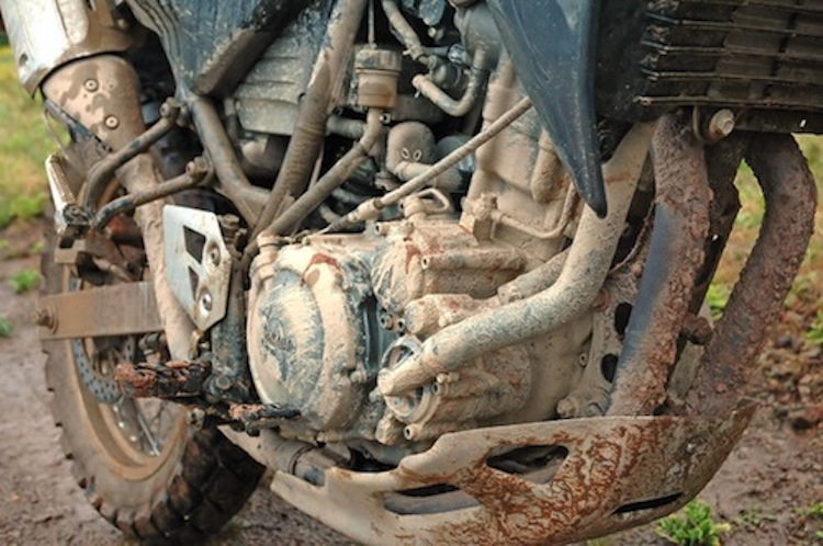 motorcycle covered in dirt, encrusted in mud